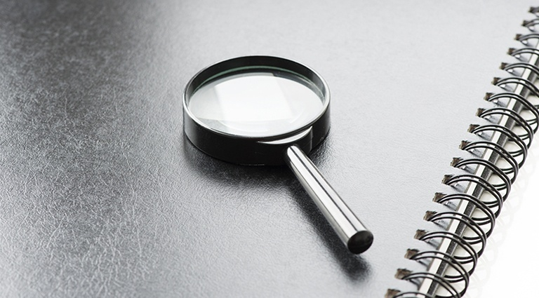 Magnifying glass on spiral notebook