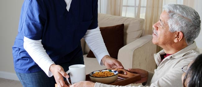 Caregiver serving food to resident