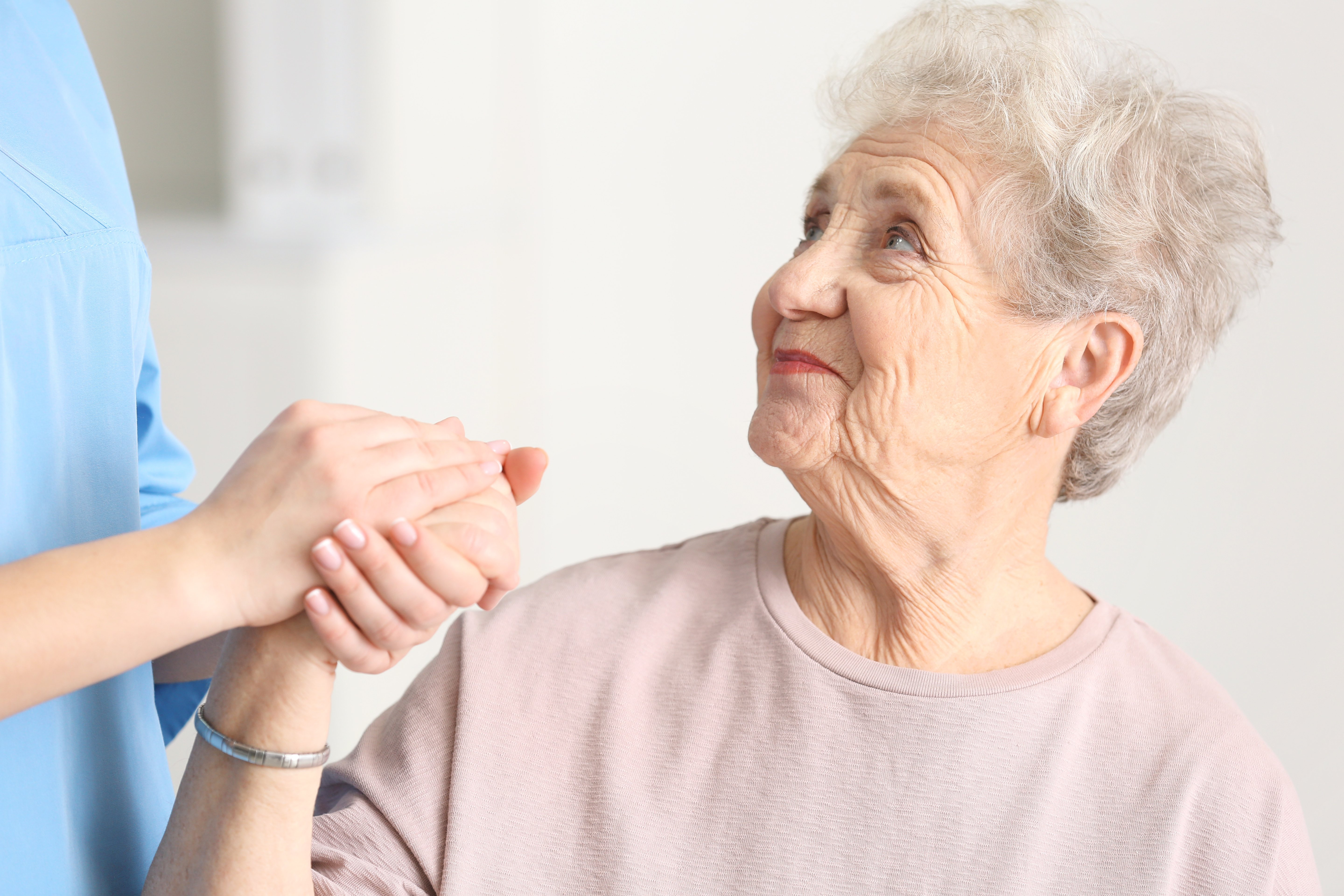 Senior woman holding a caregivers hand