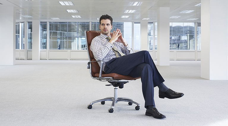 Young entrepreneur sitting on office chair in empty office