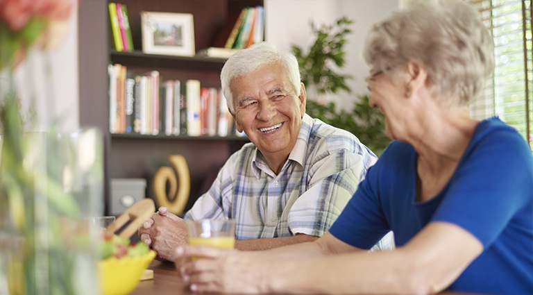 Elderly couple at a table smiling