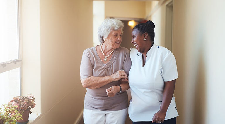 Caretaker smiling and walking with resident