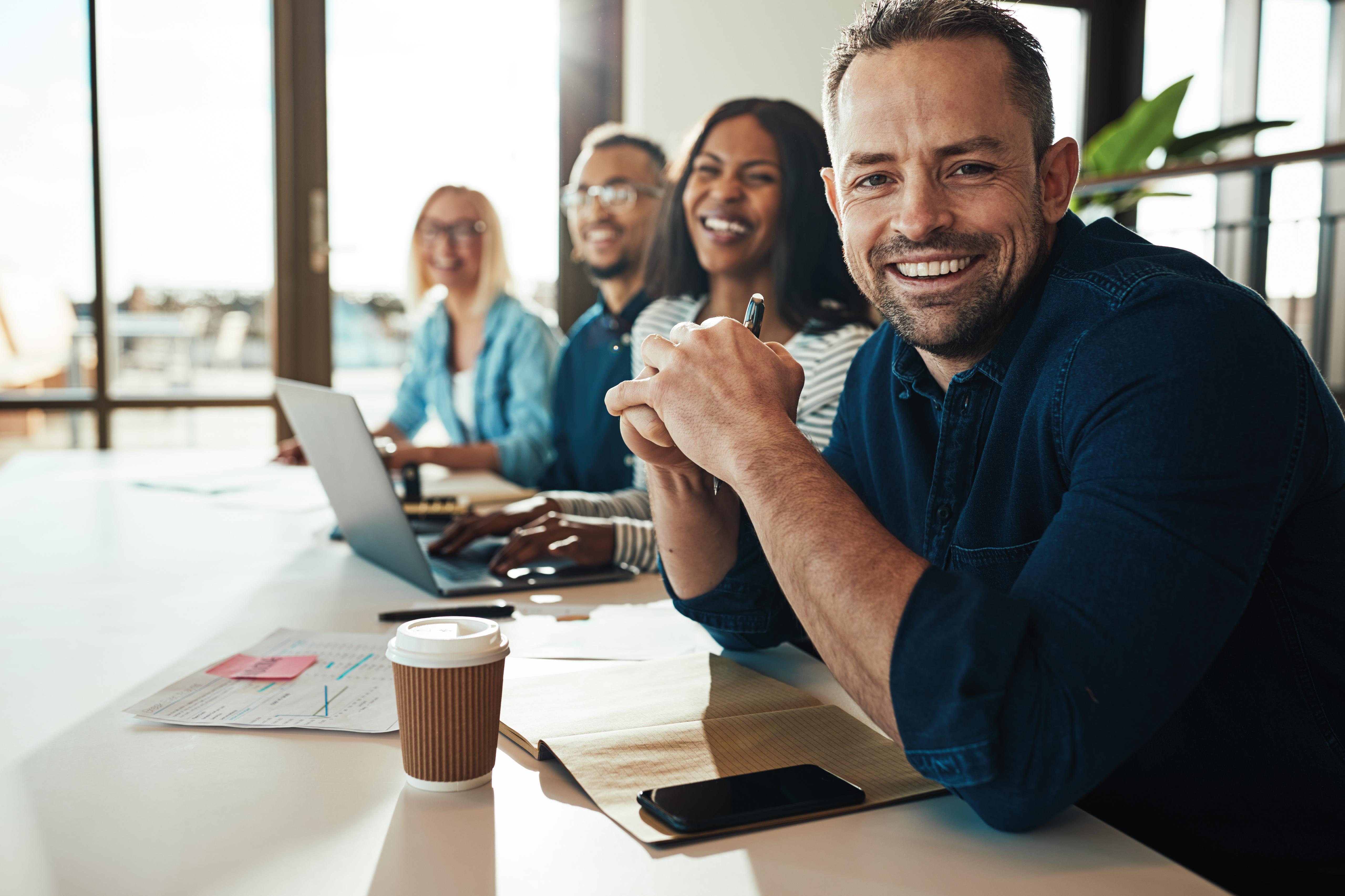 team sitting at desk smiling